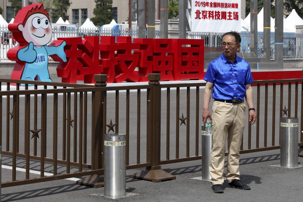 圖/一名男子站在中國軍事博物館外北京科技週「科技強國」標語前。(AP Photo / Ng Han Guan / 達志影像)